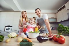 A happy family prepares food  in the kitchen. A happy family prepares food from vegetables in the kitchen Stock Photo