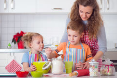 Happy family preparing cookies for Christmas eve Stock Images