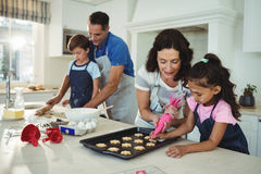 Happy family preparing cookies in kitchen Royalty Free Stock Images