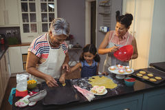 Happy family preparing desserts in kitchen Stock Photography