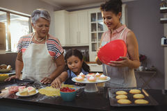 Happy family preparing desserts in kitchen Royalty Free Stock Photography