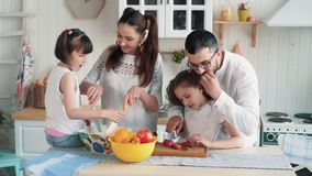 Happy family preparing food on kitchen, cutting vegetables, slow motion