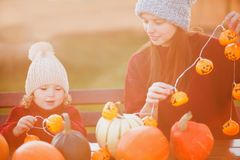 Mother and child choosing pumpkins for jack-o-lantern. Royalty Free Stock Photo