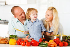 Happy family preparing a healthy dinner at home. Happy family is preparing a healthy dinner in the kitchen royalty free stock images