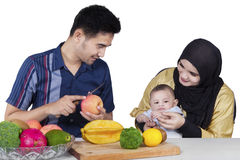 Happy Family Preparing A Meal. Portrait of happy family preparing a meal and having fun, on white background stock image