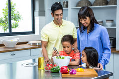 Happy family preparing salad in the kitchen Stock Image