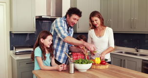 Happy family preparing salad together stock video footage