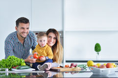 Happy family preparing vegetables together at home in the kitchen stock photo