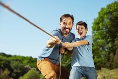 Happy family pulling a rope in the park. Best team. Inspired loving father helping his son while he pulling a rope with his sister Royalty Free Stock Photo