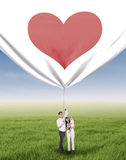 Happy family pulling valentine banner Royalty Free Stock Image