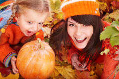 Happy family with pumpkin on autumn leaves. stock photography