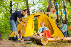 Happy family putting up a tent together in woods Stock Photos