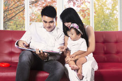 Happy family read a book on sofa. Hispanic family reading a story book on sofa at home in autumn Royalty Free Stock Image