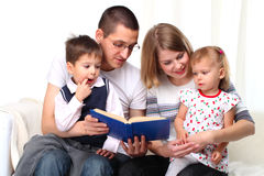 Happy Family Reading A Book On Sofa Royalty Free Stock Images