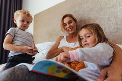 Happy family reading a bedtime storybook. Young mom with her children on bed reading a story book. Cute little girl pointing at storybook while sitting with her Royalty Free Stock Photos