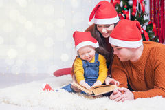 Happy family reading a book with christmas fairy tale Stock Photography