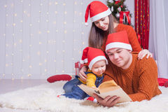 Happy family reading a book with christmas fairy tale Stock Photos
