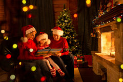 Happy family reading a book by a Christmas tree in Royalty Free Stock Images