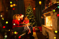 Happy family reading a book by a Christmas tree in Stock Images
