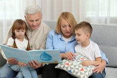 Happy family reading book. On couch Stock Image