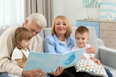 Happy family reading book. On couch Stock Photography
