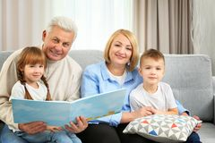 Happy family reading book. On couch Royalty Free Stock Photography