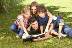 Happy family reading book in garden. Happy family with children reading a book together in a garden Royalty Free Stock Images