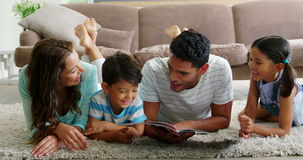 Happy family reading book in living room