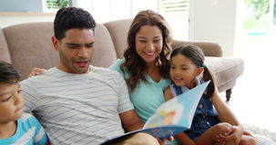 Happy family reading book in living room stock video footage