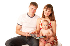 Happy family reading a book and smiling. Stock Photos