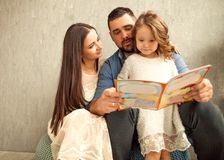 Happy family reading a book to her daughter. Mothers Day. Happy family reading a book to her daughter. Mothers Day royalty free stock photography