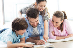 Happy family reading book together Stock Image
