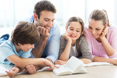 Happy family reading book together. Smiling family relaxing at home Royalty Free Stock Photography