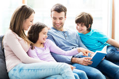 Happy family reading book together. Smiling family relaxing at home Stock Image