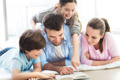 Happy family reading book together. Smiling family relaxing at home Royalty Free Stock Photo