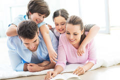Happy family reading book together. Smiling family relaxing at home Royalty Free Stock Image