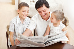 Happy family reading a newspaper Royalty Free Stock Image