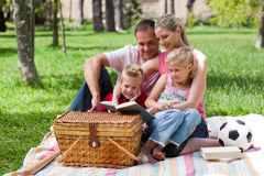 Happy family reading in a park Royalty Free Stock Photos