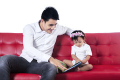 Happy family reading story book on sofa Royalty Free Stock Photo