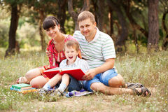 Happy family reading together. Happy father, mother and son reading book on the grass in the park. Family reading together royalty free stock photography