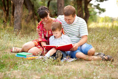 Happy family reading together. Happy father, mother and son reading a book on the lawn in the park. Family reading together royalty free stock image