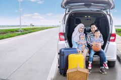 Happy family ready for a road trip. While looking at the camera and sitting together in the car trunk. Shot on the highway Stock Photography
