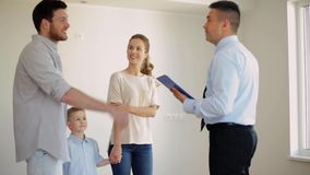 Happy family and realtor at new house or apartment. Mortgage, housing and real estate concept - happy family and realtor with clipboard showing new house or stock footage