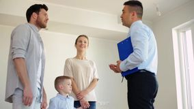 Happy family and realtor at new house or apartment. Mortgage, housing and real estate concept - happy family and realtor with clipboard showing new house or stock video footage