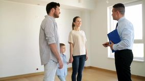 Happy family and realtor at new house or apartment. Mortgage, housing and real estate concept - happy family and realtor giving house or apartment key and stock footage