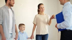 Happy family and realtor at new house or apartment. Mortgage, housing and real estate concept - happy family and realtor giving house or apartment key and stock video footage