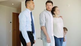 Happy family and realtor at new house or apartment. Mortgage, housing and real estate concept - happy family and realtor with tablet pc walking along new house stock footage