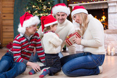 Happy family in red hats with gift sitting at. Happy family in Santa hats giving gift to youngest child sitting at Christmas tree near fireplace Stock Photo