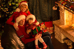 Happy family in red hats with gifts sitting at Stock Photos