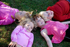 Happy family relaxation. A family group of four kids (three girls and one boy) lying in a circle in the grass and relaxing after playtime stock images
